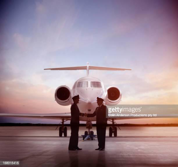 Caucasian pilots shaking hands near jet
