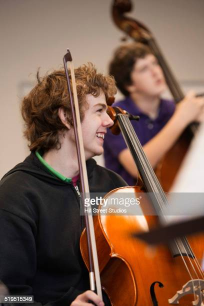 Caucasian playing upright bass in music class