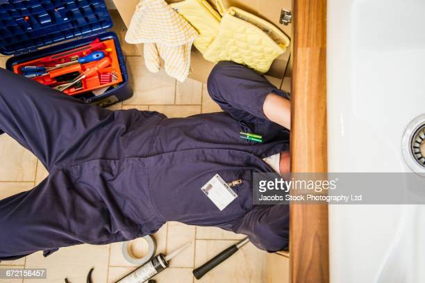 Caucasian plumber working under sink