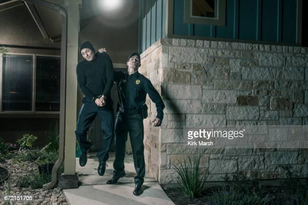 Caucasian police lifting burglar in handcuffs