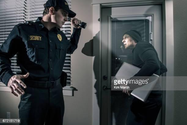 Caucasian police officer shining flashlight on burglar stealing laptop