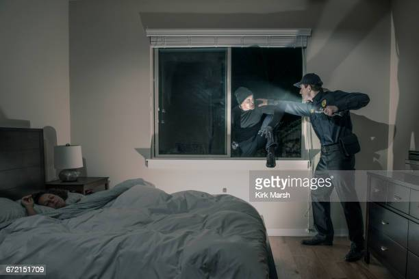 Caucasian police officer shining flashlight on house burglar