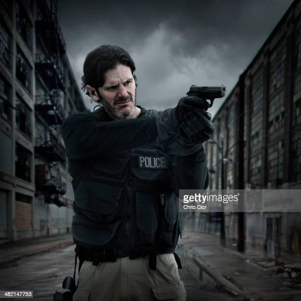 Caucasian policeman aiming gun on city street
