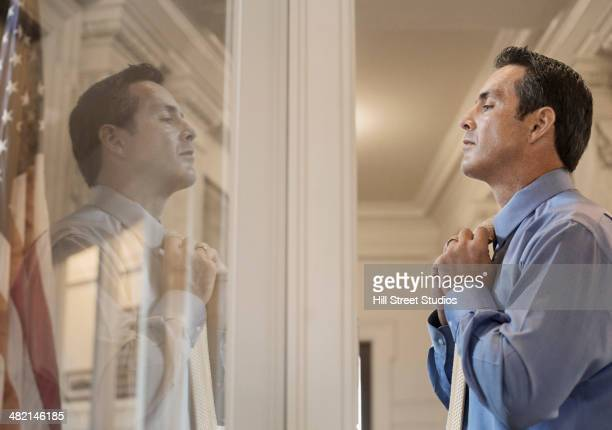 Caucasian politician adjusting his tie in window