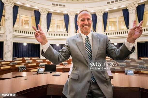 Caucasian politician gesturing victory in rotunda