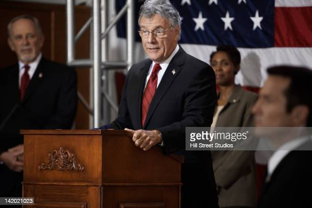 caucasian politician making speech at podium - politician stock pictures, royalty-free photos & images