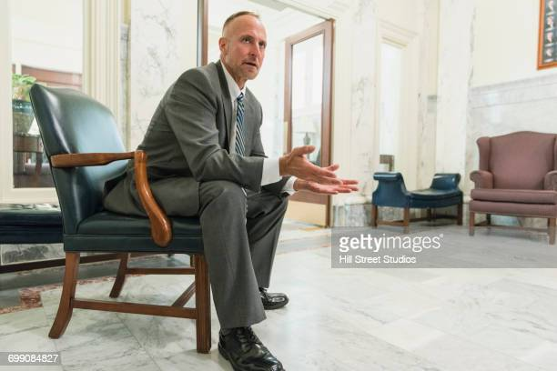 caucasian politician sitting in armchair gesturing in office - 身ぶり ストックフォトと画像