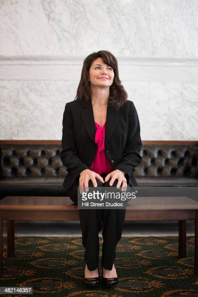 Caucasian politician sitting in lobby of government building