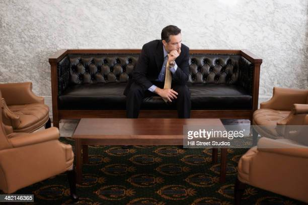 caucasian politician sitting in lobby of government building - tensed idaho stock photos and pictures