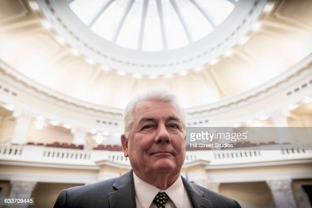 caucasian politician smiling in capitol building - politician stock pictures, royalty-free photos & images
