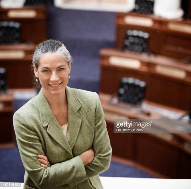 Caucasian politician smiling in chamber