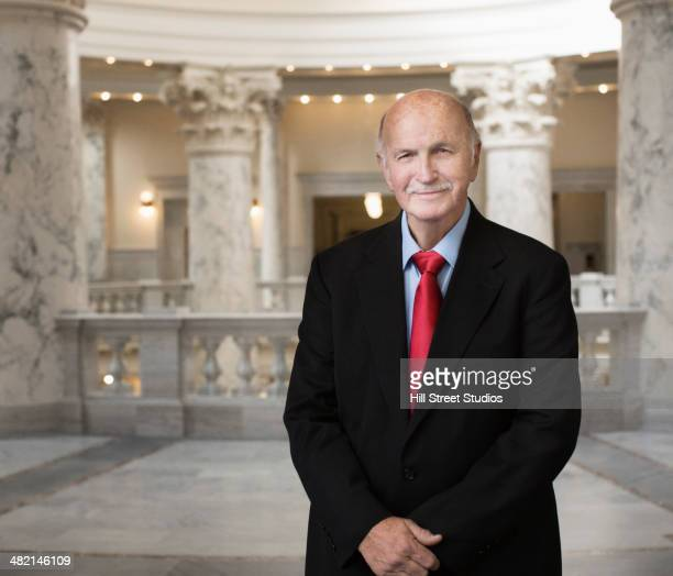 caucasian politician smiling in government building - politician stock pictures, royalty-free photos & images