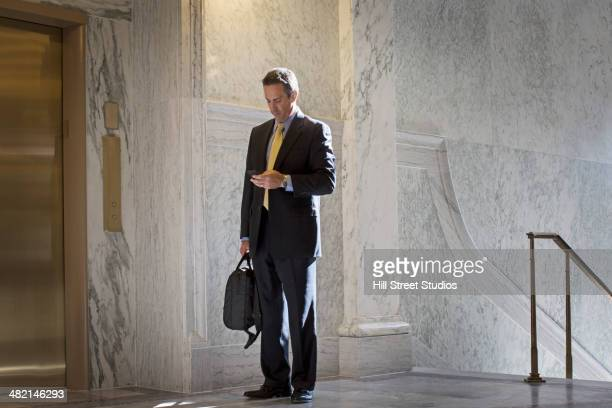 Caucasian politician using cell phone in government building