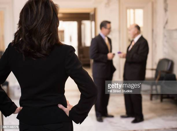 Caucasian politician watching men in government building