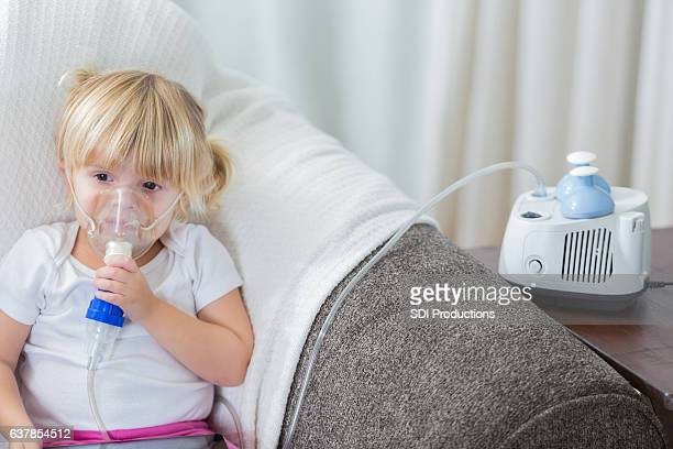 Caucasian preschool age girl with cystic fibrosis receives breathing treatment