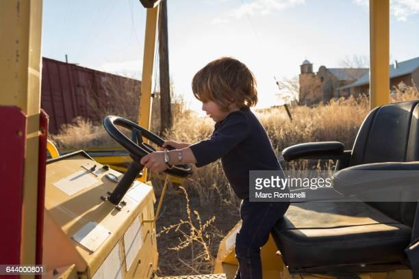 Caucasian preschooler boy driving tractor