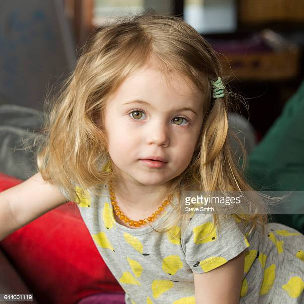 Caucasian preschooler girl sitting on sofa