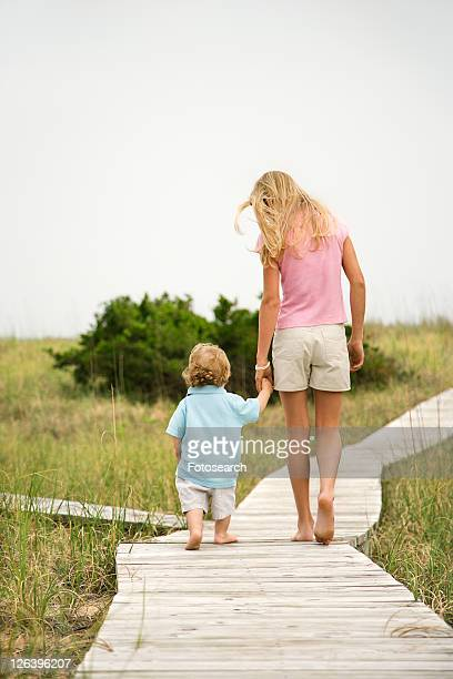 Caucasian pre-teen girl walking on beach access walkway and holding hands with Caucasian male toddler .