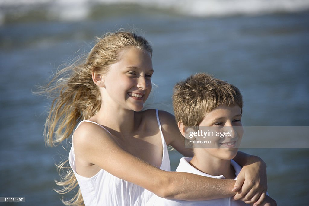 Caucasian Preteen Girl With Arms Around Preteen Boy On Beach Stock Photo  Getty Images-4452