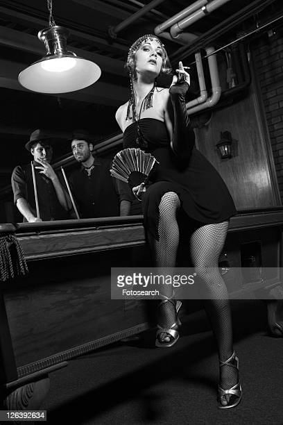 caucasian prime adult female standing in front of pool table with two caucasian prime adult men in background. - flapper stock photos and pictures