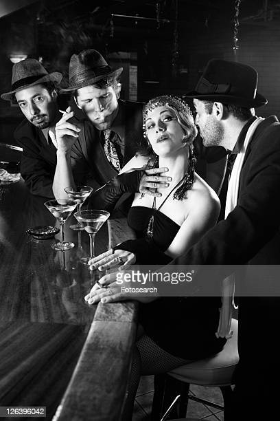 caucasian prime adult retro female sitting at bar surrounded by suitors. - flapper stock photos and pictures