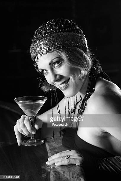 caucasian prime adult retro female sitting at bar with martini looking at viewer. - flapper stock photos and pictures