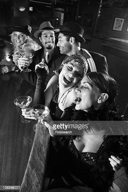caucasian prime adult retro females and males sitting at bar. - flapper stock photos and pictures