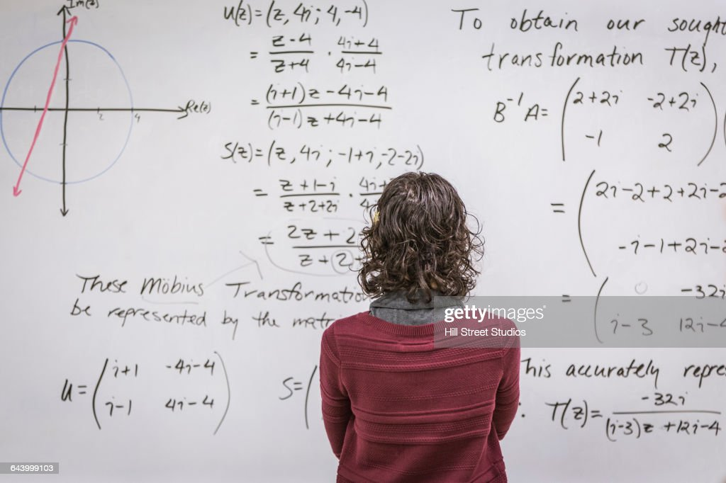 Caucasian professor examining equations on whiteboard : Stock-Foto