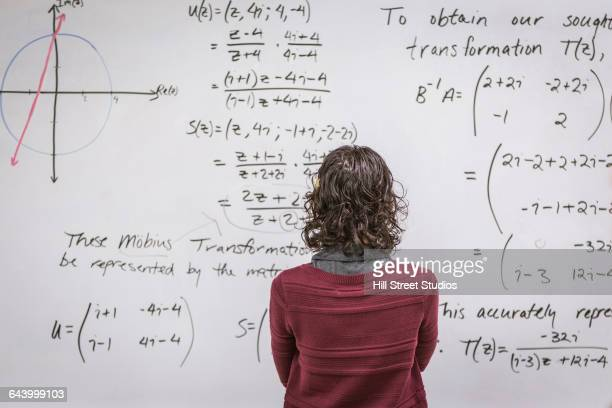 Caucasian professor examining equations on whiteboard