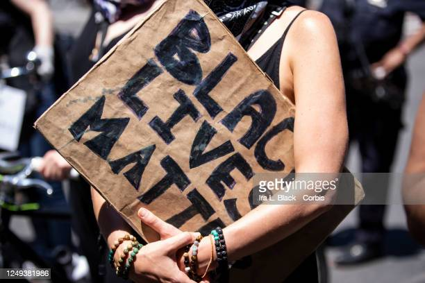 "Caucasian protester cradles in their arms a homemade sign on a box that says, ""Black Lives Matter"" during a protest at Trump Tower. This was part of..."