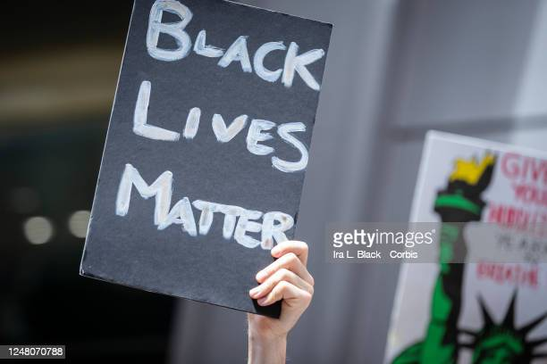 "Caucasian protester holds a handmade sign that reads, ""Black Lives Matter"" in a similar way to another sign with the Statue Of Liberty in Times..."