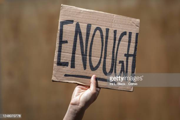 "Caucasian protester in Times Square holds a handmade sign that reads, ""Enough"". This was part of the Black Lives Matter New York protest that offered..."