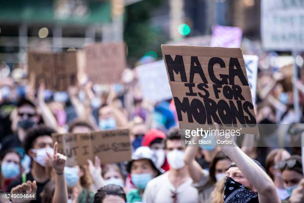 "Caucasian protester wearing a mask holds a homemade sign that says, ""MAGA Is for Morons"" in the middle of the crowd that gathered at Columbus Circle...."