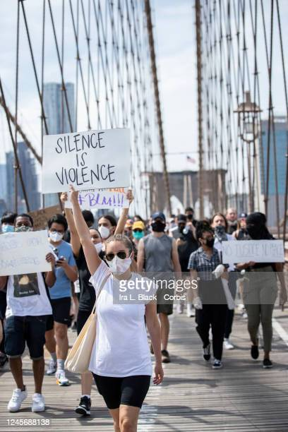 "Caucasian protester wearing a mask holds a sign that says, ""Silence is Violence"" with the arch of the Brooklyn Bridge behind them as they walk across..."