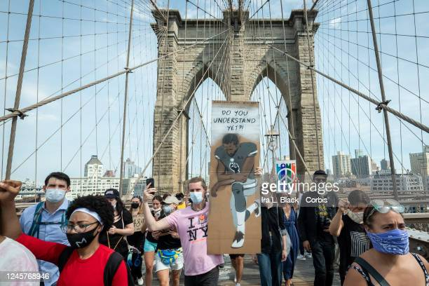 """Caucasian protester wearing a mask holds a sign that says,""""Do You Understand Yet?"""" with a picture of Colin Kaepernick, former quarterback for the San..."""