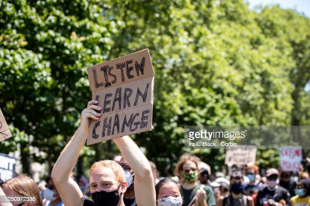 """Caucasian protester wearing a mask holds their homemade sign that reads, """"Listen Learn Change"""" as they clap to the speakers comments on the lawn at..."""