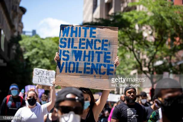 "Caucasian protester wearing a mask holds up a homemade sign on a box that says, ""White Silence is White Violence"" during a protest march to Gracie..."