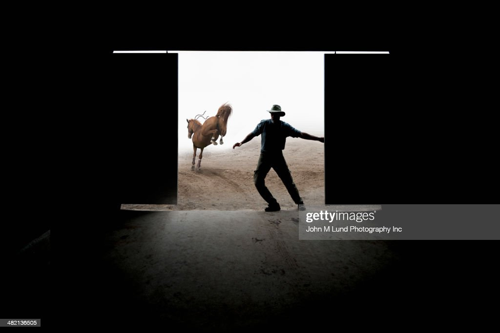 Caucasian rancher closing barn door : Stock Photo