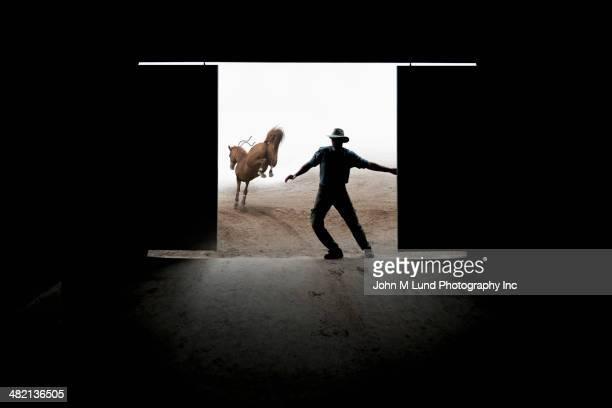 Caucasian rancher closing barn door