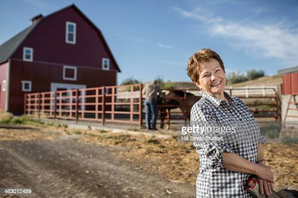 Caucasian rancher standing by barn