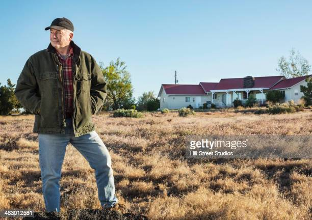 Caucasian rancher standing in field