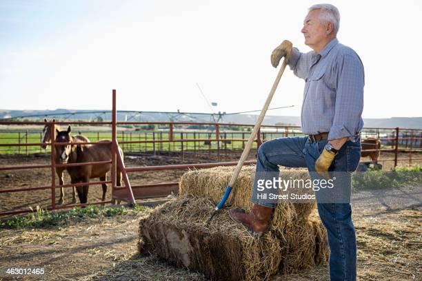 Caucasian rancher standing near horse corral