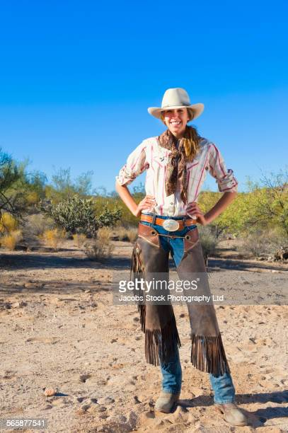 Caucasian rancher wearing leather chaps on dirt path