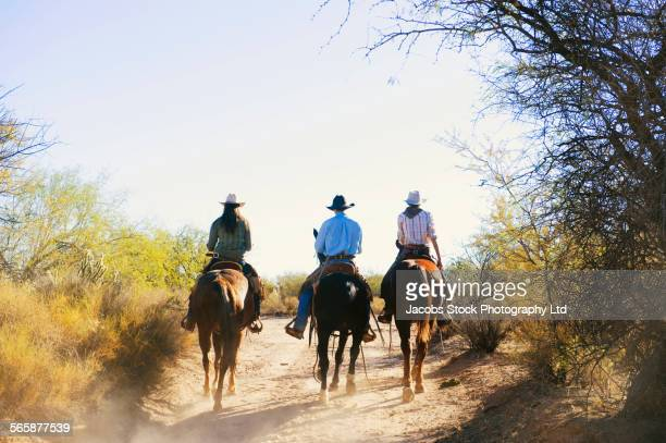 Caucasian ranchers riding horses on dirt path