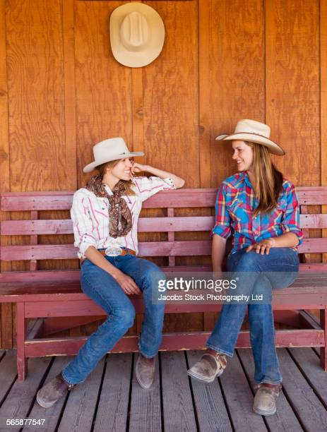 Caucasian ranchers talking on wooden bench
