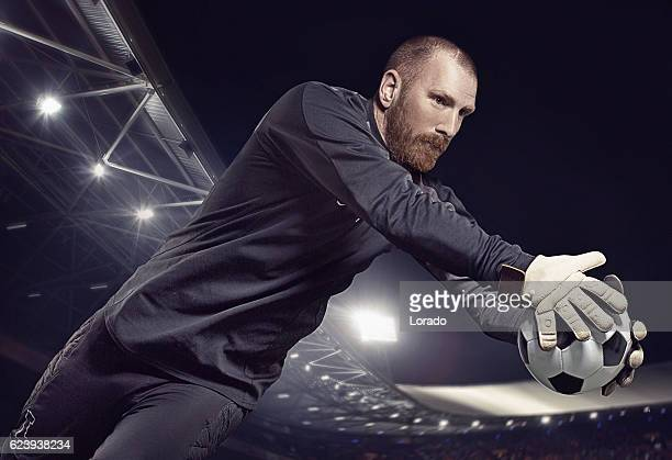 caucasian redhead adult male soccer player goalkeeper saving football - marquer un but photos et images de collection