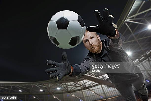 caucasian redhead adult male soccer player goalkeeper saving football - goalkeeper stock pictures, royalty-free photos & images