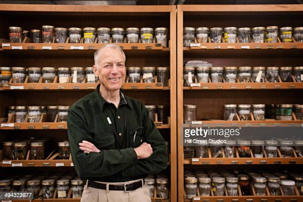Caucasian researcher smiling with specimens in museum