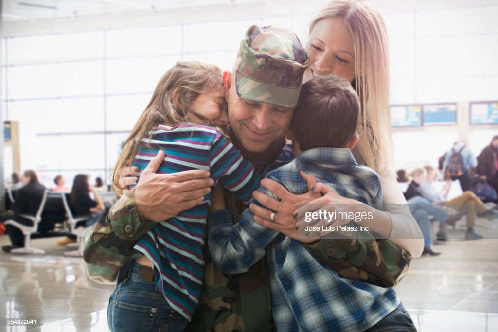 Caucasian returning soldier greeting family : Stock Photo
