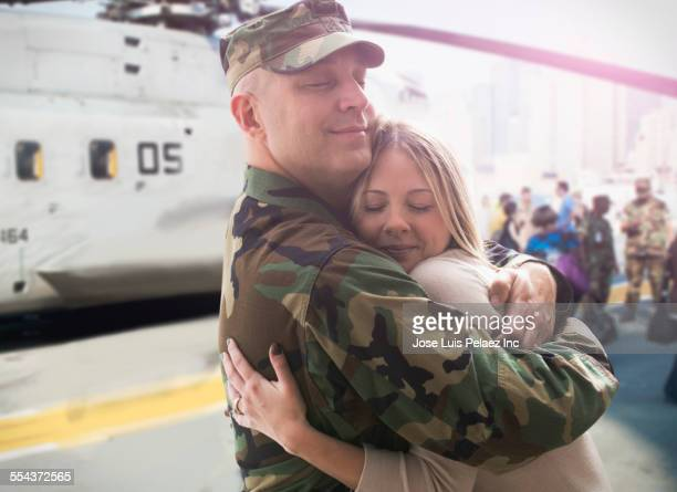Caucasian returning soldier hugging wife near helicopter